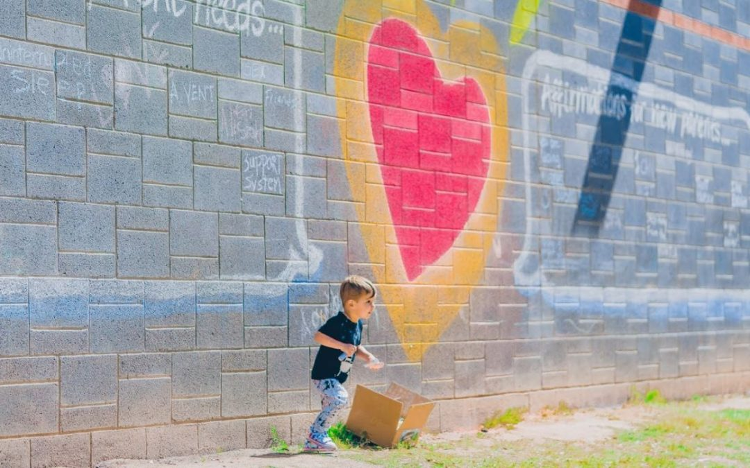 child in front of 4th Trimester Arizona logo chalk art wall